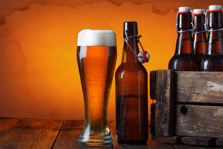 grunge bottle: Beer glass with wooden crate full of beer bottles on table Stock Photo