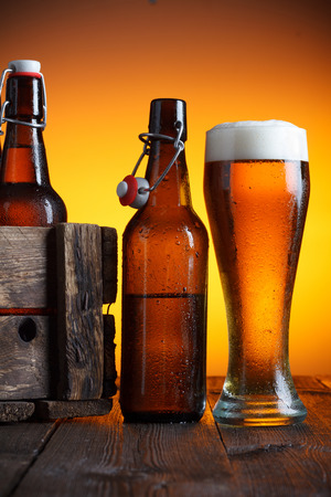 Beer glass and beer crate with bottles on wooden table still life photo