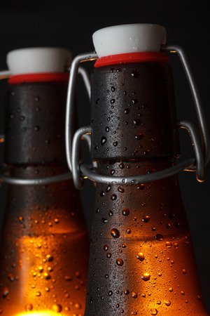grunge bottle: Two beer bottles on dark