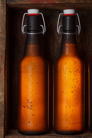 Beer bottles with vintage swing tops in old wooden crate still life photo