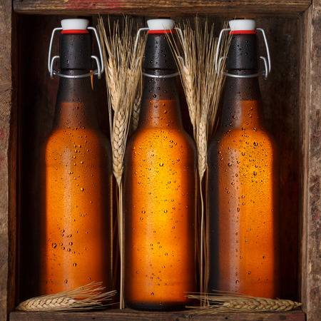 Beer bottles with wheat stems in old wooden crate still life photo