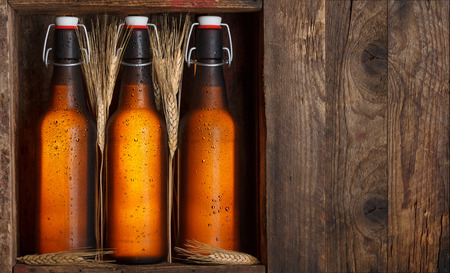 Beer bottles with wheat stems in old wooden crate still life, with copy space photo