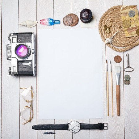 White blank paper sheet with lot of different creative stuff around it on wooden table photo