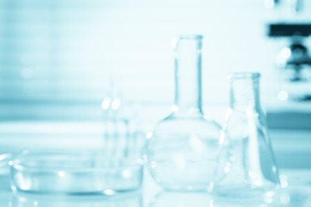 Blurred science background, test tubes and microscope, research concept Imagens