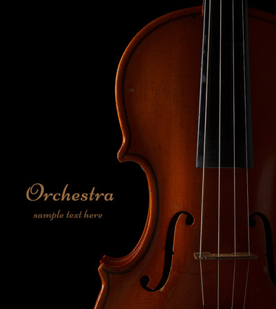 a symphony: Violin detail in ambient light on black background with copy space