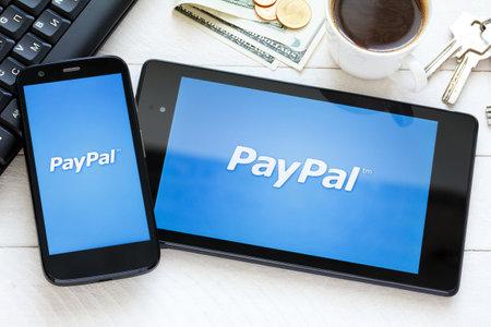 KIEV, UKRAINE - June 9: PayPal payment system logo on tablet and new smarphone, in Kiev, Ukraine, on June 9, 2014.