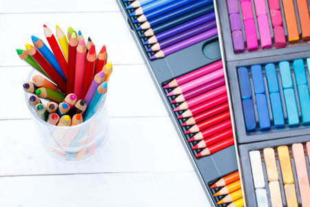 pencil box: Multi colored pencils in jar on wooden table, with pastel and pencils box on background