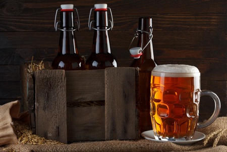 Beer glass with beer bottles in wooden crate on burlap cloth photo