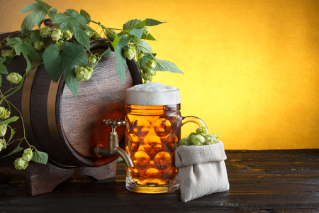 Wooden beer barrel with fresh hop cones and glass of beer on table still life photo