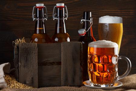 Bierglas en krat met flessen bier op jute doek met gerstzaden