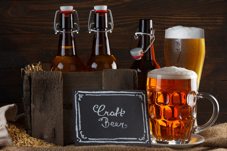 Craft beer glass and vintage wooden crate with beer bottles on burlap cloth with barley seeds photo