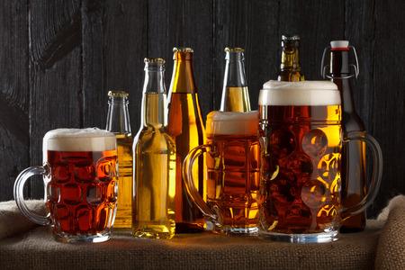 botellas de cerveza: Surtido de vasos de cerveza en la mesa con una tela de arpillera, fondo de madera oscura