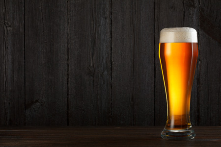 Glass of beer on wooden table, dark background with copy space photo