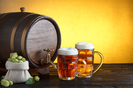 beer barrel: Vintage beer barrel with two beer glasses and burlap bag with fresh hops on wooden table still life with copy space