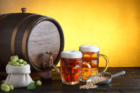 Vintage beer barrel with two beer glasses and bag full of fresh hops, with metal scoop with barley on wooden table still life, copy space photo