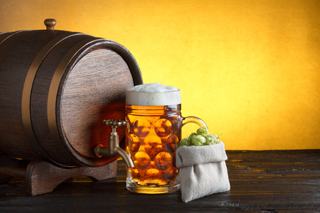 Vintage beer barrel with huge glass of beer and burlap bag with fresh hops on wooden table still life photo