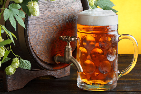 Beer barrel with fresh hops on it and beer glass on wooden table still life photo