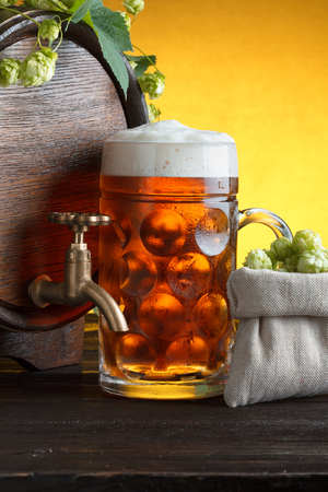 Wooden beer barrel with fresh hop cones and glass of beer on table close up photo