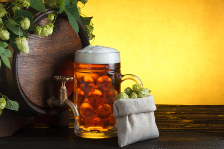 Beer barrel with fresh hop cones and glass of beer on table still life photo