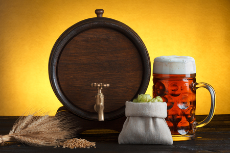 Vintage beer barrel with beer glass and fresh hops, with wheat on wooden table still life photo