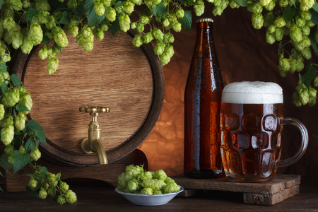 brewing: Bottled and unbottled beer with barrel and fresh hops for brewing still-life Stock Photo