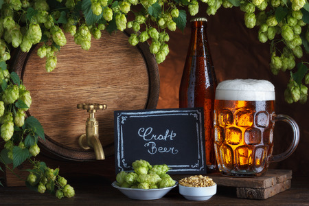 glass beer bottle: Craft bottled and unbottled beer with barrel, barley and fresh hops for brewing still-life