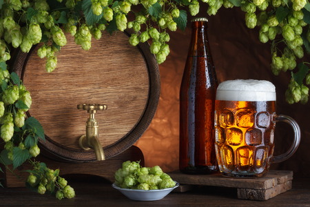 Bottled and unbottled beer with barrel and fresh hops for brewing still-life photo