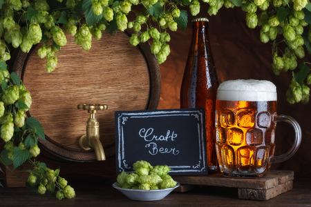 unbottled: Bottled and unbottled beer with barrel and fresh hops for brewing still-life Stock Photo