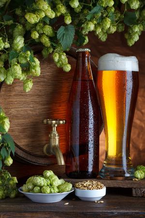 unbottled: Bottled and unbottled beer with barrel, barley and fresh hops for brewing still-life