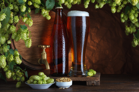 Bottled and unbottled beer with barrel, barley and fresh hops for brewing still-life photo