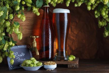 unbottled: Craft bottled and unbottled beer with barrel, barley and fresh hops for brewing still-life