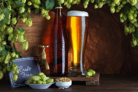 Craft bottled and unbottled beer with barrel, barley and fresh hops for brewing still-life