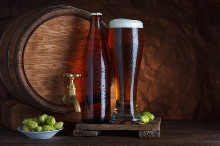 Bottled and unbottled beer glass with barrel and fresh hops for brewing still-life photo