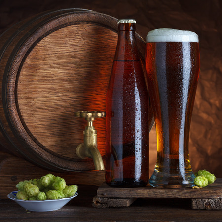 Bottled and unbottled beer glass with vintage old barrel and fresh hops for brewing still-life