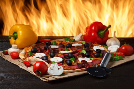 stone cutter: Hot pizza with oven fire on background