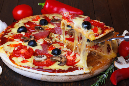 melted cheese: Pizza slice with melted cheese on lifter