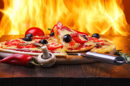 Pizza on wooden table with one slice on a lifter, real oven fire on backgroud