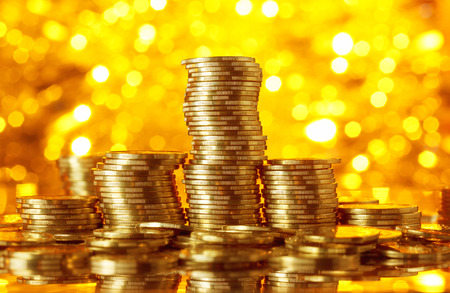 Golden coins stacks on bright light glowing bokeh background, business finance wealth and success concept Banco de Imagens