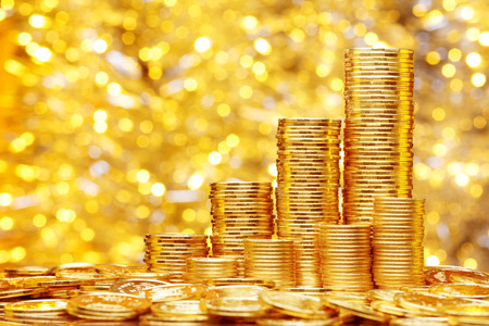 Sparkling new golden coins stacks on bright light glowing bokeh background, business finance wealth and success concept