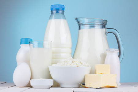 chees: Natural organic dairy products, milk, cottage cheese, eggs, butter, yoghurt, butter and sour cream on white wooden bale and blue background still life