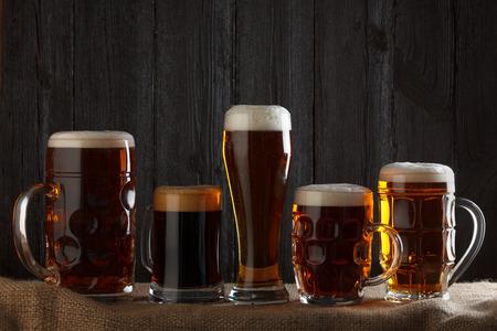 cerveza negra: Vasos de cerveza con la cerveza dorada, cerveza oscura, negra, la malta y cerveza negra en la mesa, el fondo de madera oscura Foto de archivo