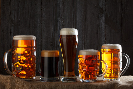 mug of ale: Beer glasses with lager, dark lager, brown ale, malt and stout beer on table, dark wooden background