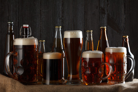 Beer glasses and bottles with lager, dark lager, brown ale, malt and stout beer on table, dark wooden background Imagens
