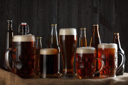 Pivní sklenice a láhve s ležák, tmavý ležák, hnědé pivo, slad a tlusté pivo na stůl, tmavé dřevěné pozadí