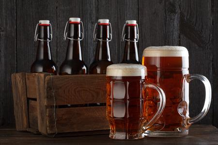 Bierglas met vintage houten doos vol met beeer flessen op houten tafel stilleven Stockfoto