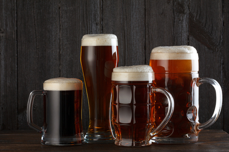 ale: Beer glasses with lager, dark lager, ale, stout beer on table, dark wooden background