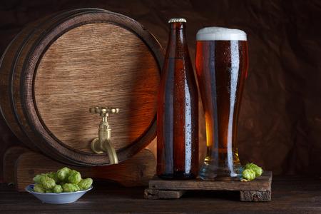unbottled: Bottled and unbottled beer glass with barrel and fresh hops for brewing on wooden table still-life