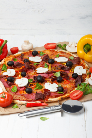 wood cutter: Pizza on wooden table with ham, salami, tomato and chili pepper, mushrooms with pizza cutter