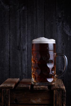 verticales: Jarra de cerveza enorme en el cajón de madera de la vendimia con el fondo de madera oscura