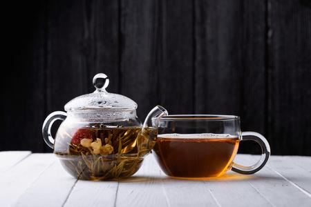 Glazen theepot met bloeiende groene thee en kopje thee op een witte houten tafel en een donkere achtergrond